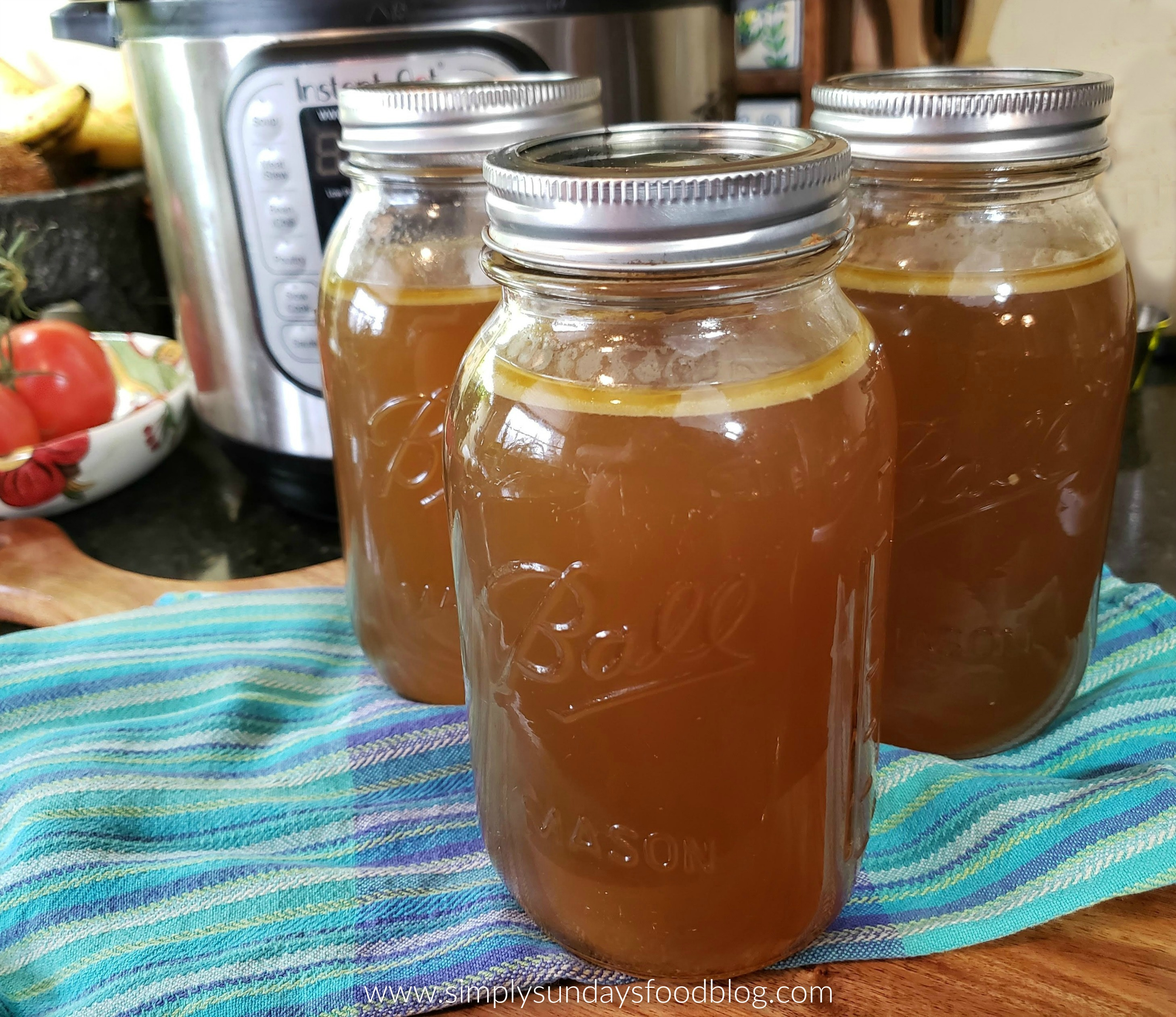 Three mason jars of homemade chicken stock with Instant Pot in backround