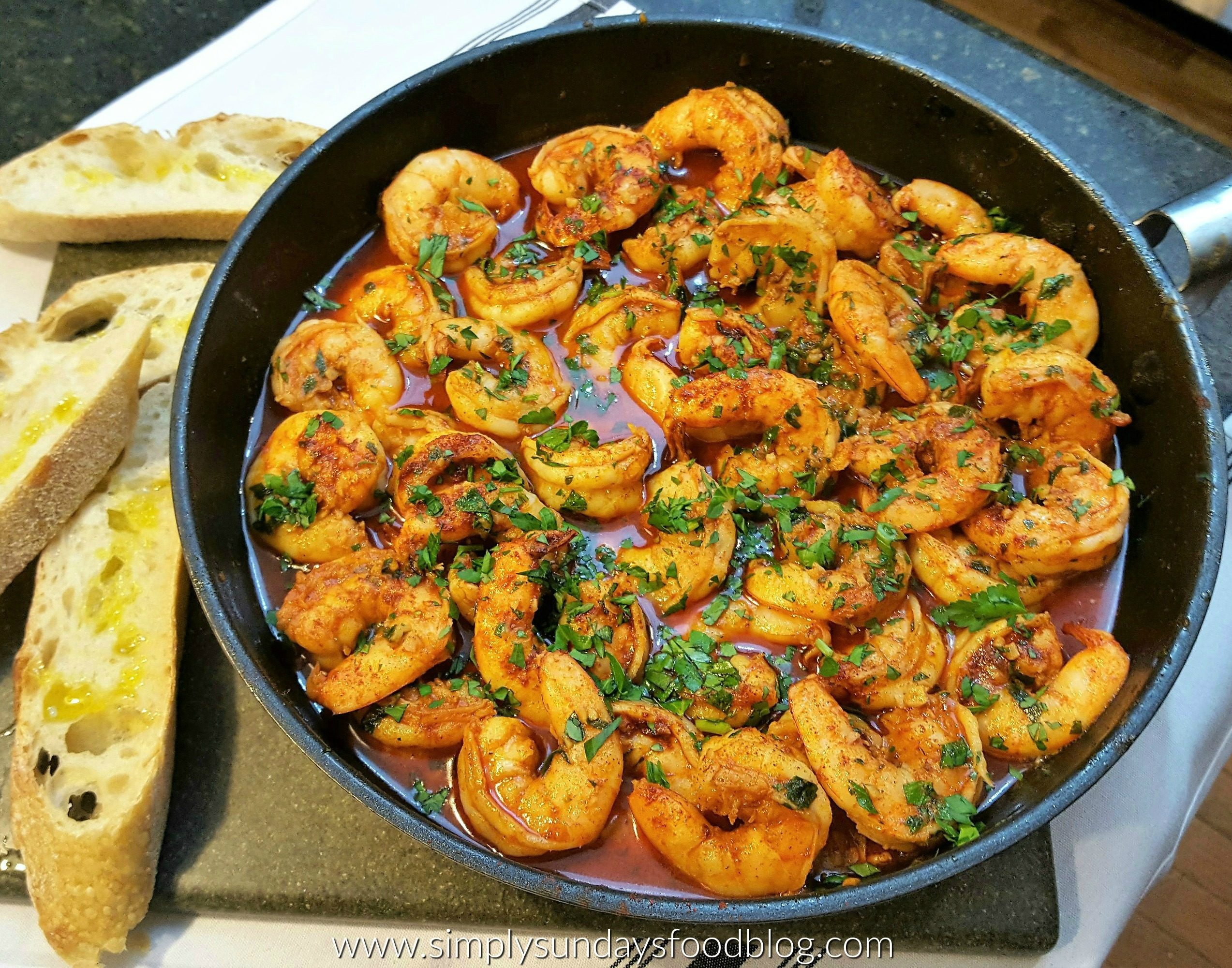 A pan filled with large shrimp coated in a red garlic sauce sprinkled with fresh green parsley with crusty garlic bread on the side drizzled with olive oil