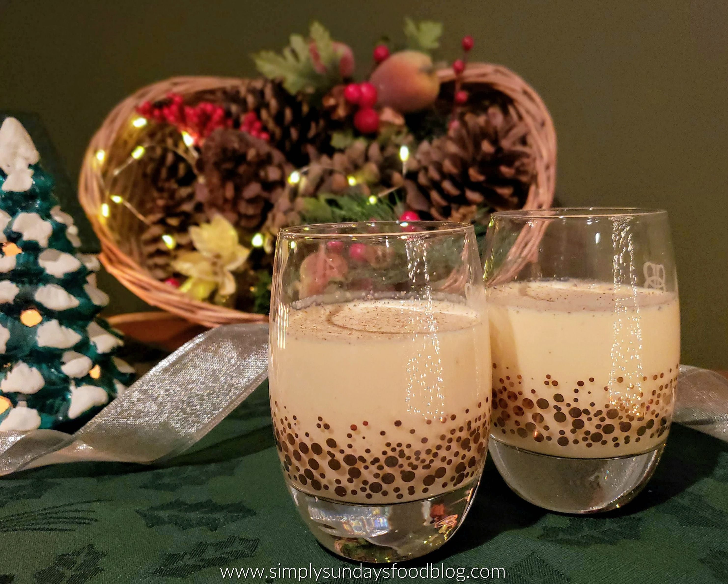 Two glasses of spiked eggnog on a green cloth with sparkling lights, pine cones and small Christmas decor in a basket in the background