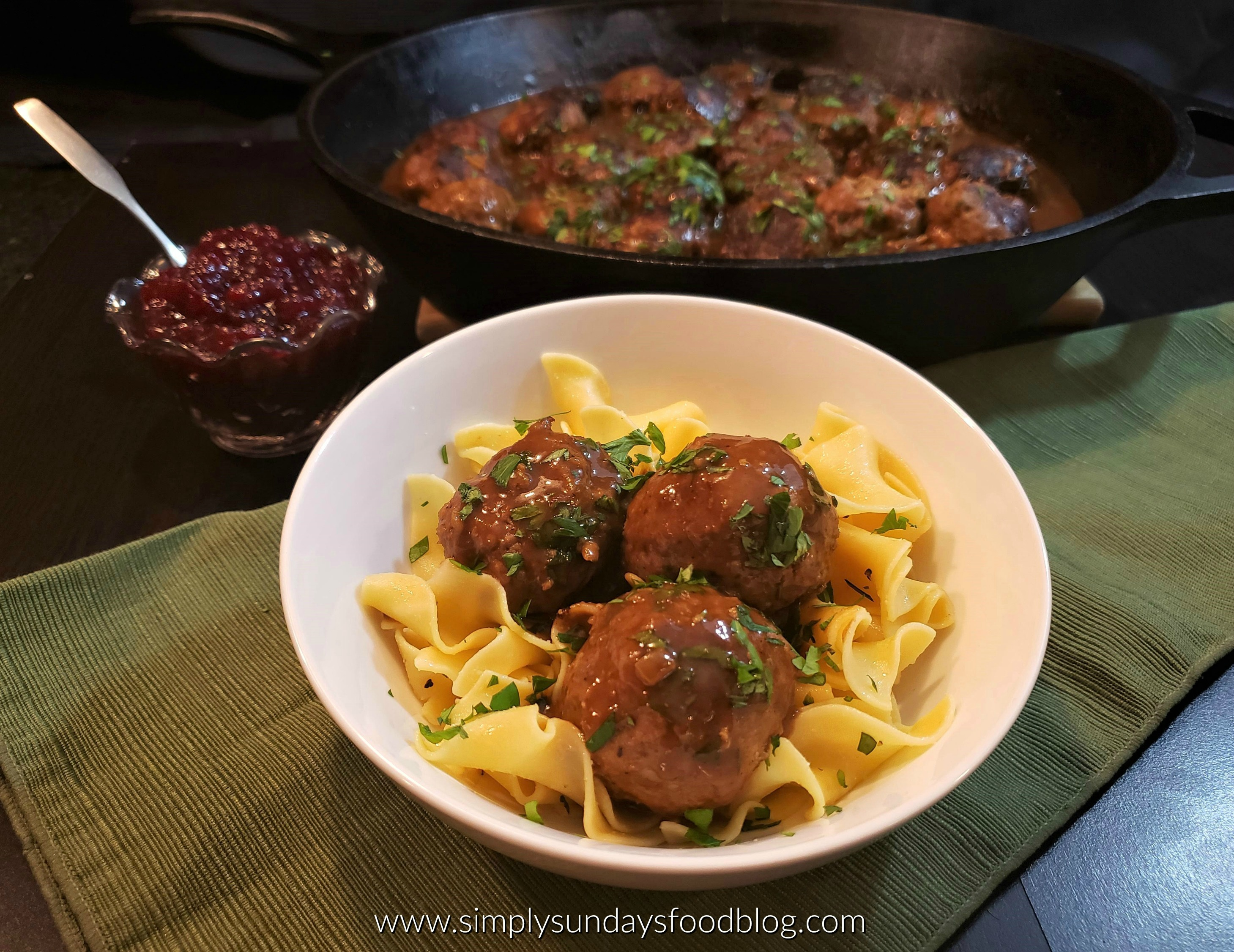 A green cloth with a white bowl on top. In the bowl is a bed of yellow cooked egg noodles. Nestled in the egg noodles are three swedish meatballs in gravy sprinkled with fresh green chopped parsley. In the background is is a large black cast iron pan filled with the rest of the meatballs. In a small bowl is purplish lingonberry jam with a silver spoon sticking out.