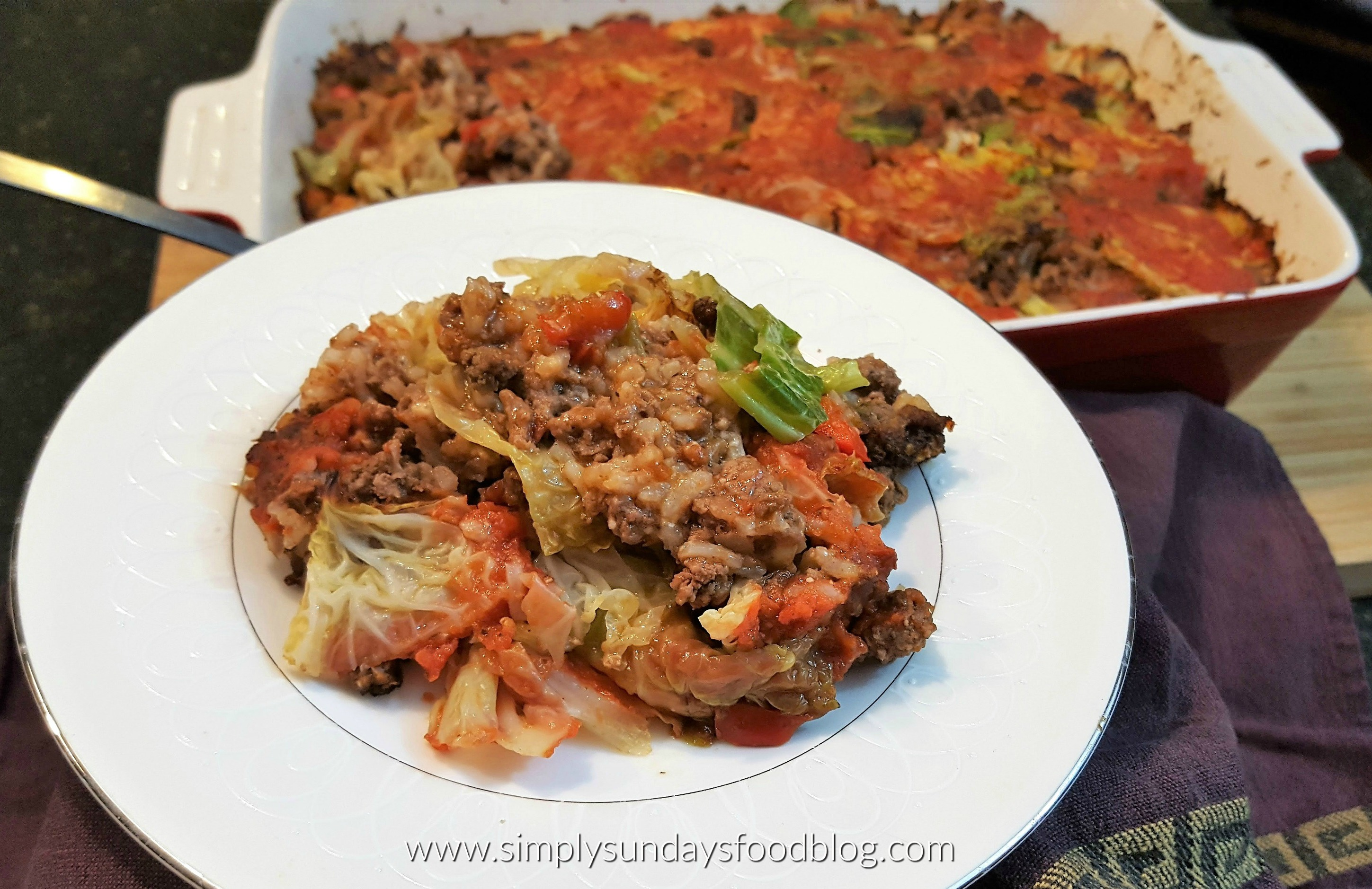 A plate of stuffed cabbage casserole on a white plate with the casserole dish in the background