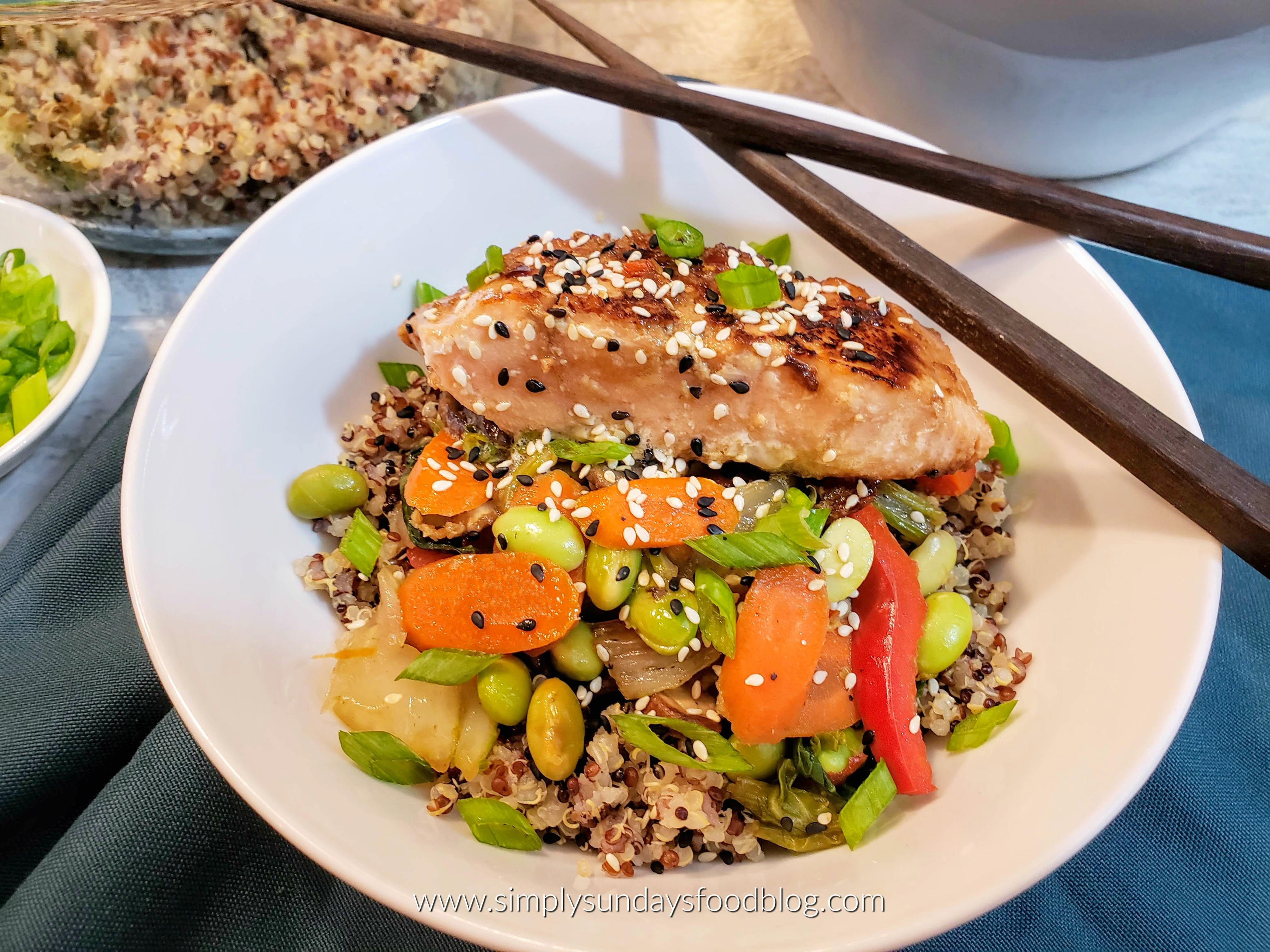 A bowl of Teriyaki marinated pan seared salmon with sauteed carrots, bok choy , red peppers and edamame over quinoa with chopsticks over a blue tablecloth