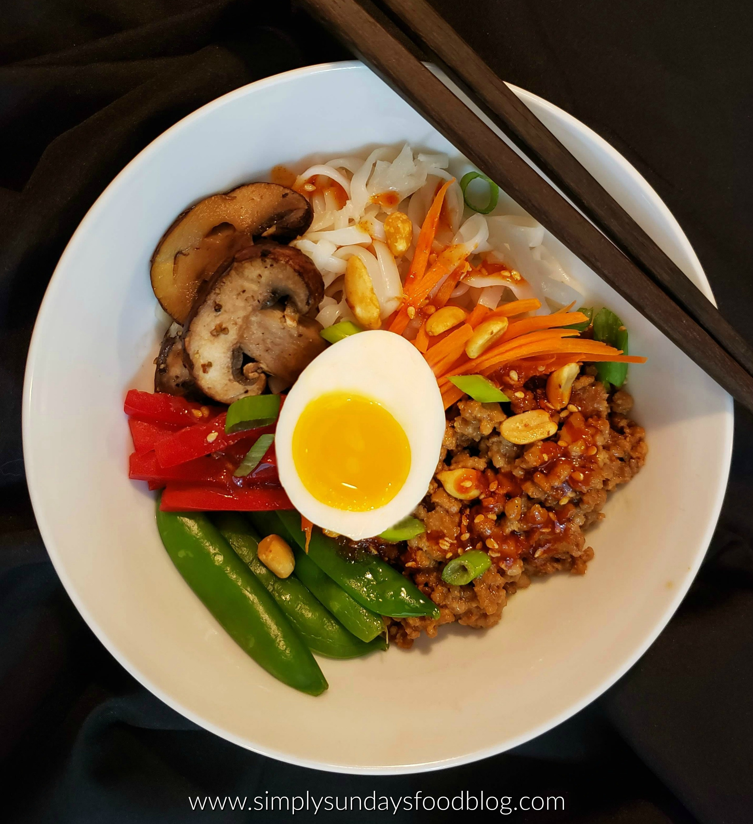 A white bowl on a black background filled with browned ground pork, white rice noodles, green sugar snap peas, bright red sliced bell pepper, browned mushrooms, orange shredded carrots with a perfectly cooked soft boiled egg halh on top drizzled with a go ju jang and sesame sauces and dry roasted peanuts