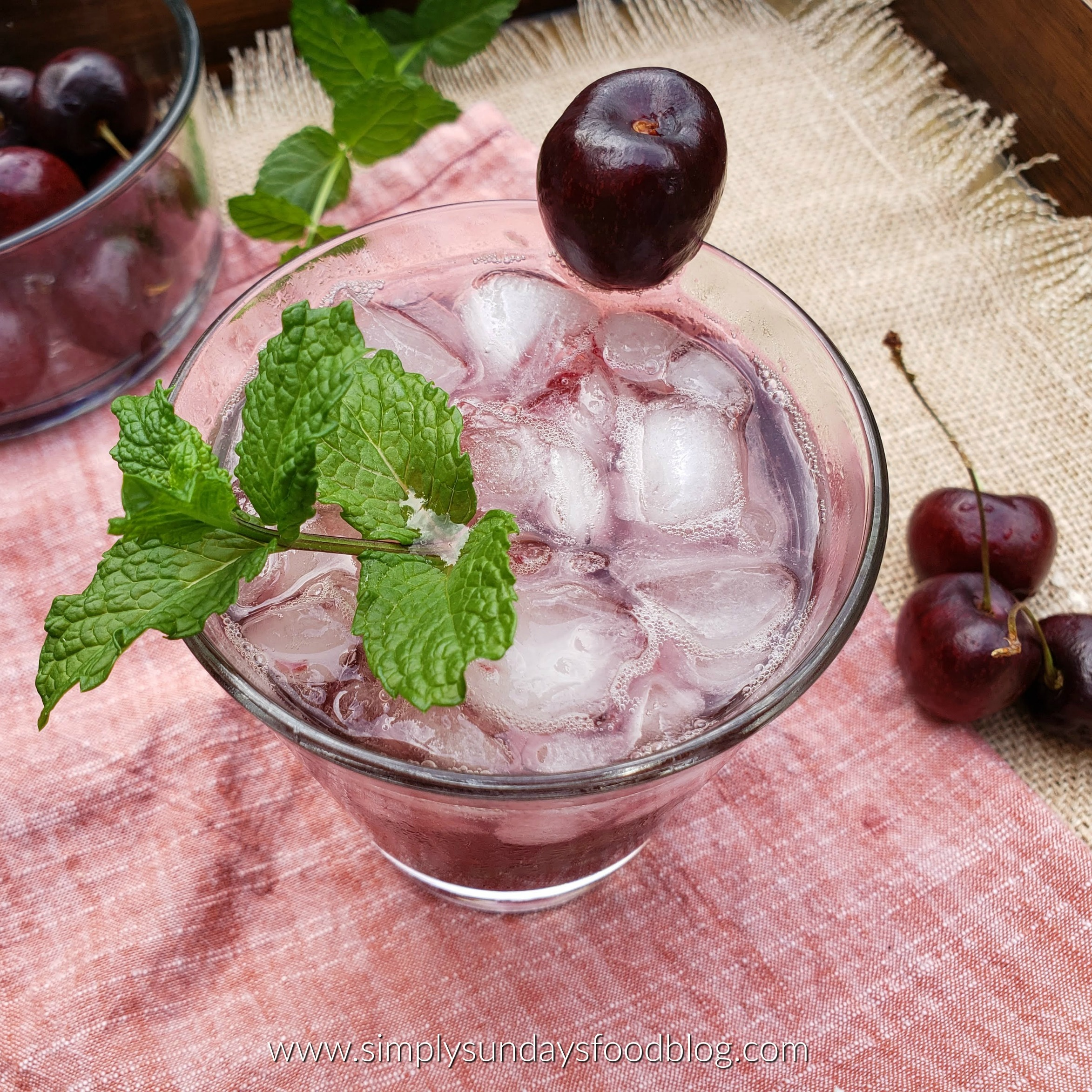 A cocktail glass with a Whiskey Cherry Smash garnished with fresh mint and a cherry