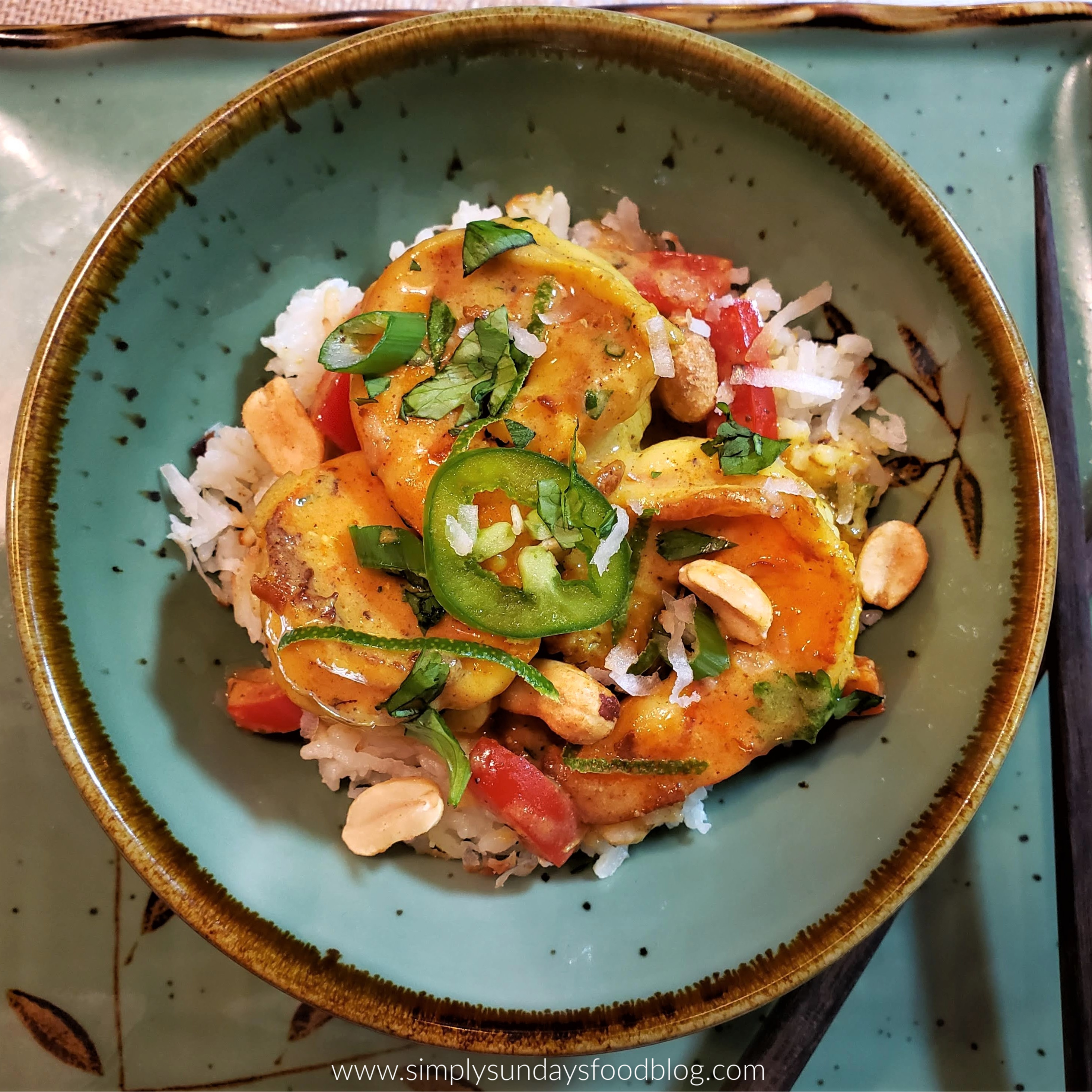 Large pink shrimp, in red curry over white rice topped with green scallions, sliced jalapenos, roasted peanuts, toasted coconut, chopped fresh green basil and cilantro